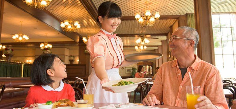 イーストサイド・カフェの料理を運ぶキャストと食事を楽しむ親子