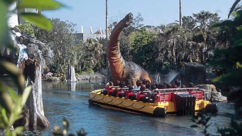 ボートに乗って恐竜の世界を探検するゲスト